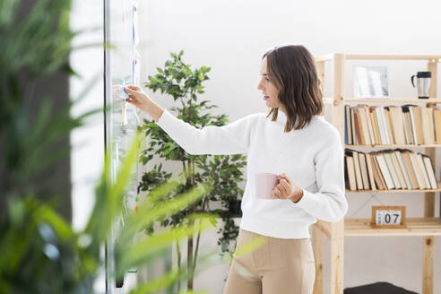 Businesswoman with coffee cup putting adhesive note on whiteboard while standing at office - GIOF09366