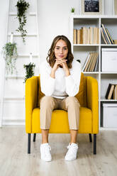 Smiling businesswoman sitting with head in hands on sofa at office - GIOF09396