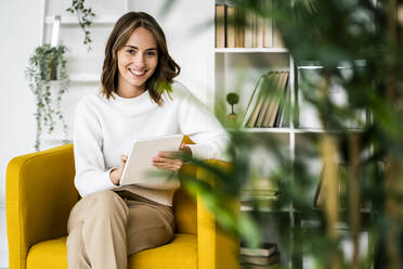 Smiling businesswoman using digital tablet while sitting on sofa at office - GIOF09399