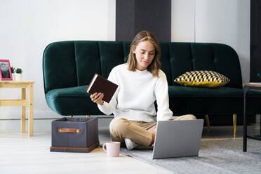 Businesswoman with book using laptop while sitting by box on floor at office - GIOF09405