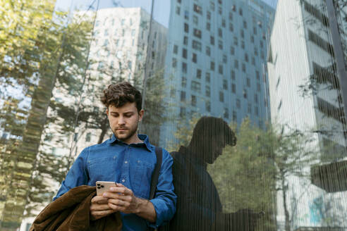 Handsome young businessman using smart phone while leaning on glass wall of modern office building - VABF03769