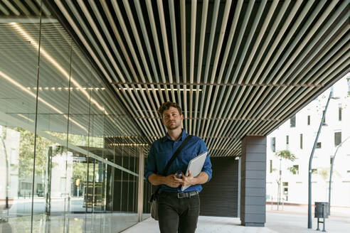Young businessman walking with laptop on walkway at modern office building - VABF03787