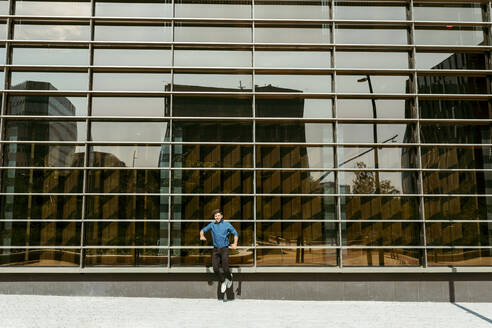 Carefree businessman jumping on footpath against modern office building - VABF03793