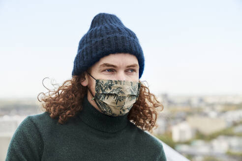 Thoughtful man with curly long hair wearing protective face mask and beanie on rooftop - FMKF06652
