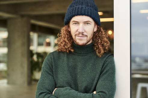 Handsome male hipster wearing knit hat while leaning on window at studio apartment - FMKF06658