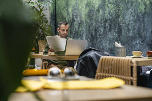 Businessman holding paper while working on laptop at cafe - VPIF03189
