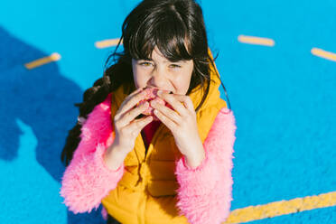 Girl eating donut while sitting on basketball court - ERRF04656