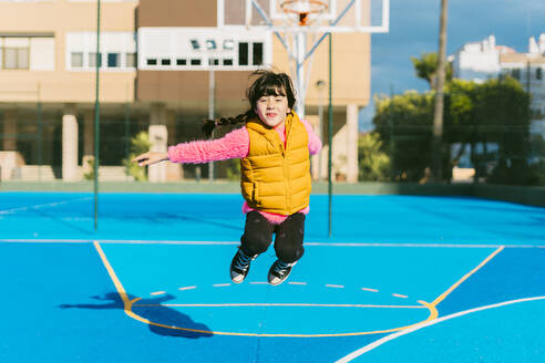 Cheerful girl jumping at sports court during sunny day - ERRF04659