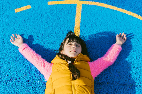 Girl relaxing with arms raised on basketball court - ERRF04662