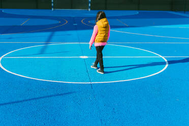 Girl in warm clothing standing on soccer court during sunny day - ERRF04668