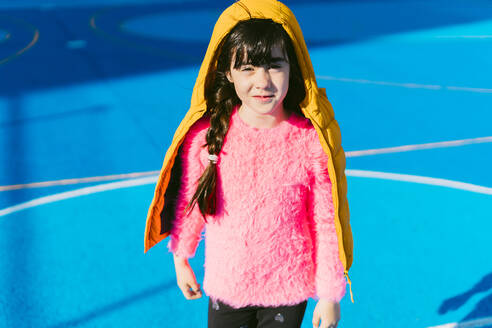 Cute girl wearing padded jacket while standing on sports court - ERRF04671