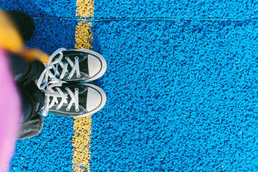 Girl standing on yellow line on blue sports court - ERRF04674