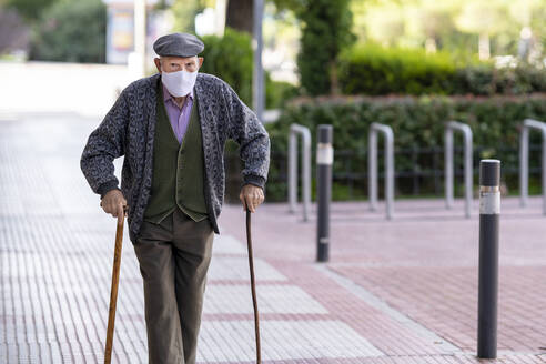 Senior man wearing protective face mask walking on footpath during COVID-19 - GGGF00023