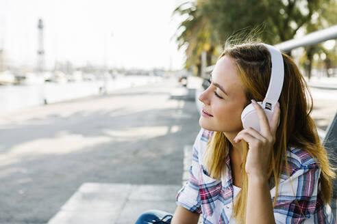 Young woman listening music through headphone sitting on footpath during sunny day - XLGF00674