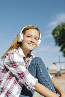 Smiling woman listening music on headphone sitting on footpath during sunny day - XLGF00677