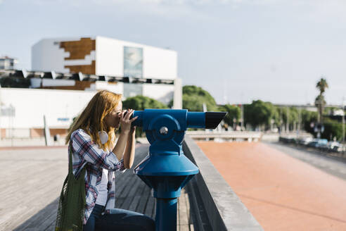 Young woman looking through binoculars while sitting on footpath during sunny day - XLGF00689
