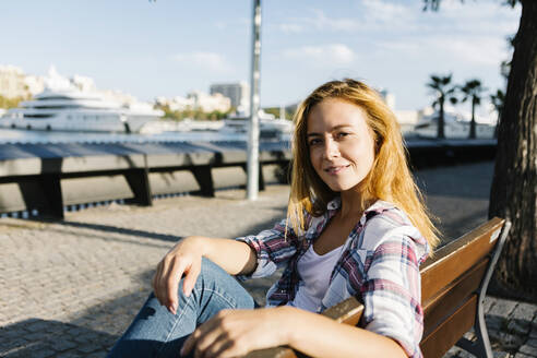 Young woman sitting on bench during sunny day - XLGF00701