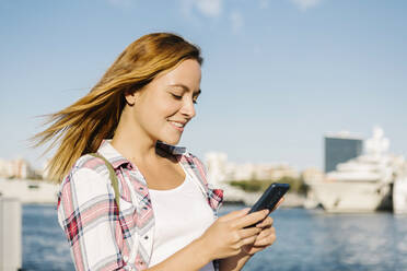 Woman text messaging on smart phone while standing at seaside during sunny day - XLGF00704