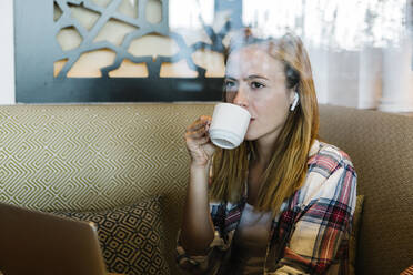 Woman looking away while drinking coffee sitting at home - XLGF00713