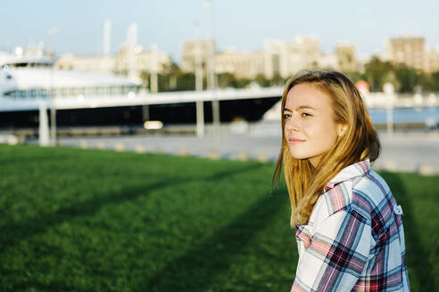 Blond woman looking away while standing in public park on sunny day - XLGF00719