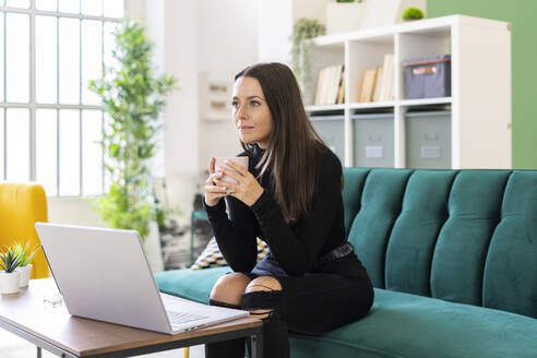 Thoughtful young woman holding coffee cup while sitting with laptop on sofa in loft apartment - GIOF09413