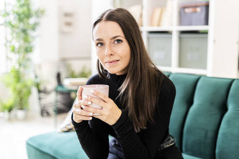 Beautiful young woman holding coffee cup while sitting on sofa in living room at home - GIOF09416