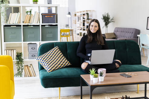 Young female blogger sitting with laptop on sofa at loft apartment - GIOF09425