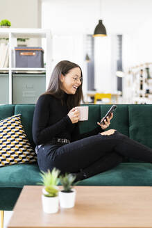 Happy female blogger using phone while sitting with coffee cup on sofa at home - GIOF09434