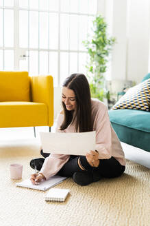 Smiling young woman writing in note pad while sitting with coffee cup on carpet against sofa at loft apartment - GIOF09473