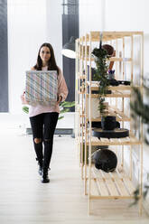 Beautiful young woman carrying box while walking by rack at loft apartment - GIOF09479