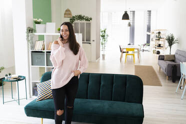 Happy beautiful young woman talking on mobile phone while standing in living room at loft apartment - GIOF09482