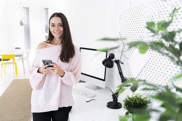 Smiling young female influencer standing with mobile phone at computer desk in loft apartment - GIOF09488
