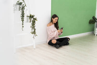 Smiling woman text messaging through mobile phone while sitting on floor by ladder against wall - GIOF09494