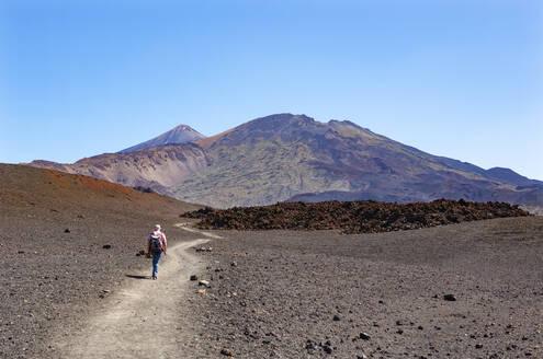 Senior man hiking along trail stretching across brown barren landscape of Tenerife island - WWF05556