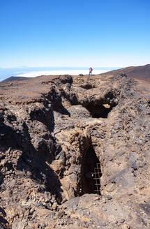 Senior hiker standing at edge of brown barren cliff - WWF05562