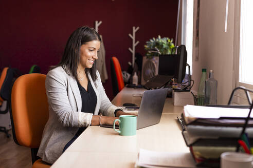 Smiling businesswoman using laptop at desk in coworking office - LJF01818
