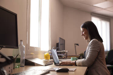 Smiling female business professional using laptop in coworking office - LJF01821