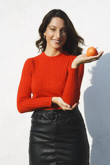 Smiling young woman holding apple while standing against wall on sunny day - NGF00685