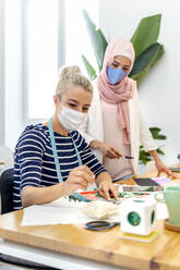 Young woman wearing face mask standing by coworker while working at office - MPPF01227