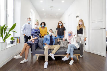Employees wearing face mask standing and sitting by sofa at office - MPPF01236