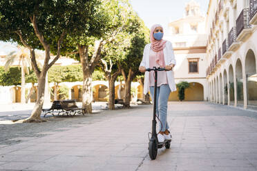 Young woman wearing face mask riding push scooter in city - MPPF01248