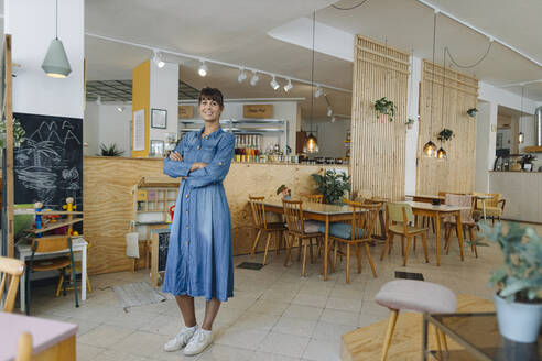 Female entrepreneur with arms crossed standing in coffee shop - GUSF04559