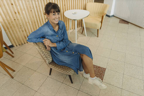 Smiling female entrepreneur sitting on chair in cafe - GUSF04562