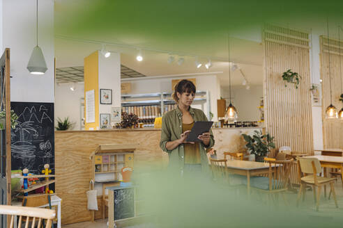 Female owner using digital tablet while standing in coffee shop - GUSF04586
