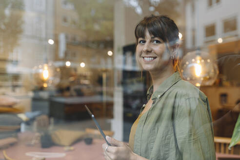 Female entrepreneur using digital table looking through window while standing in coffee shop - GUSF04589
