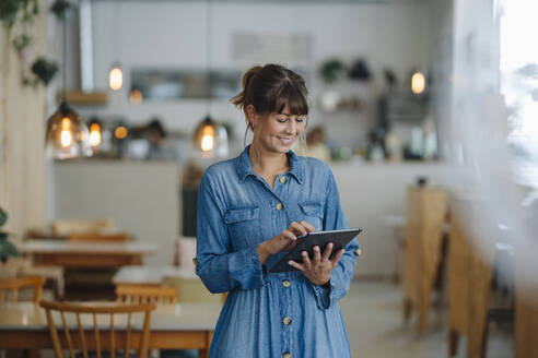 Smiling businesswoman using digital tablet while standing in coffee shop - GUSF04622