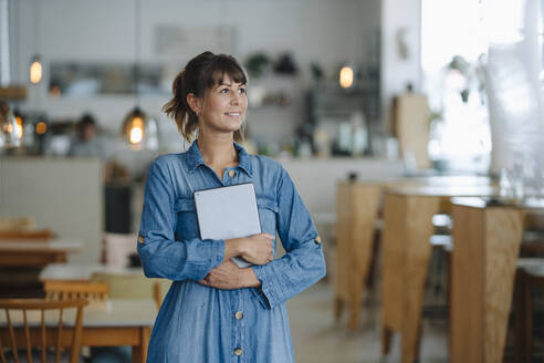 Businesswoman looking away holding digital tablet standing in coffee shop - GUSF04625