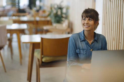 Businesswoman smiling while looking away using laptop sitting in coffee shop - GUSF04640