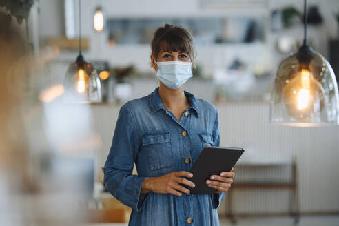 Female owner wearing protective face mask using digital tablet while standing in cafe - GUSF04646