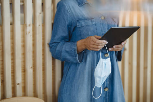 Midsection of female entrepreneur holding digital tablet and protective face mask standing in cafe - GUSF04649